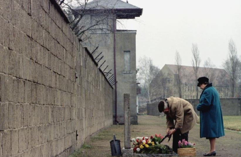An elderly couple lays a wreath in front of a memorial for the victims of the Nazi concentration camp in Sachsenhausen (photo credit: REUTERS)