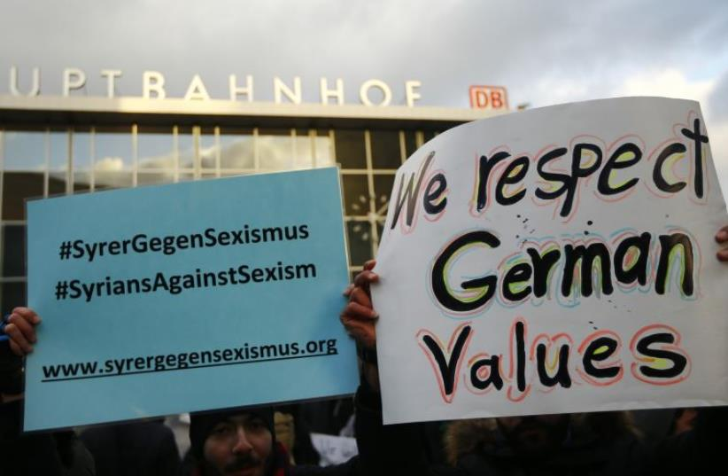 People from Syria hold placards reading 'Syrians against sexism' during a rally outside the main railway station in Cologne, Germany, January 16, 2016, where the vast majority of dozens of New Year Eve assaults on women took place.  (photo credit: REUTERS)