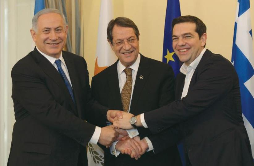 PRIME MINISTER Benjamin Netanyahu, Cypriot President Nicos Anastasiades (center) and Greek Prime Minister Alexis Tsipras shake hands ysterday outside the Presidential Palace in Nicosia, Cyprus, January 28, 2013 (photo credit: HAIM ZACH/GPO)