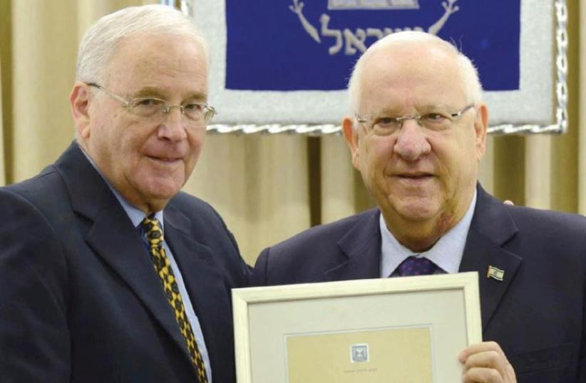 PRESIDENT REUVEN RIVLIN holds the citation for encouragement, initiative and social responsibility alongside Dr. Yitzhak Kadman, January 28, 2016 (photo credit: MARK NEYMAN / GPO)