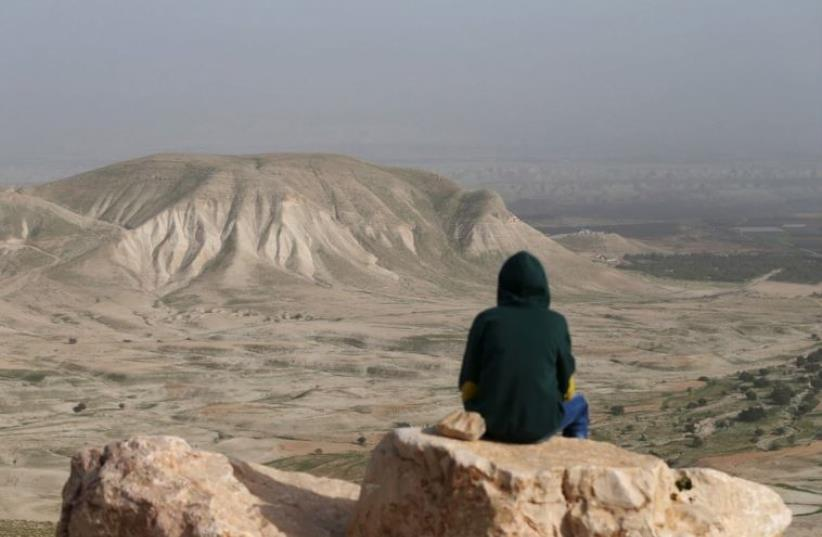 A Palestinian man sits on a rock at Jordan Valley near the West Bank city of Jericho (photo credit: REUTERS)