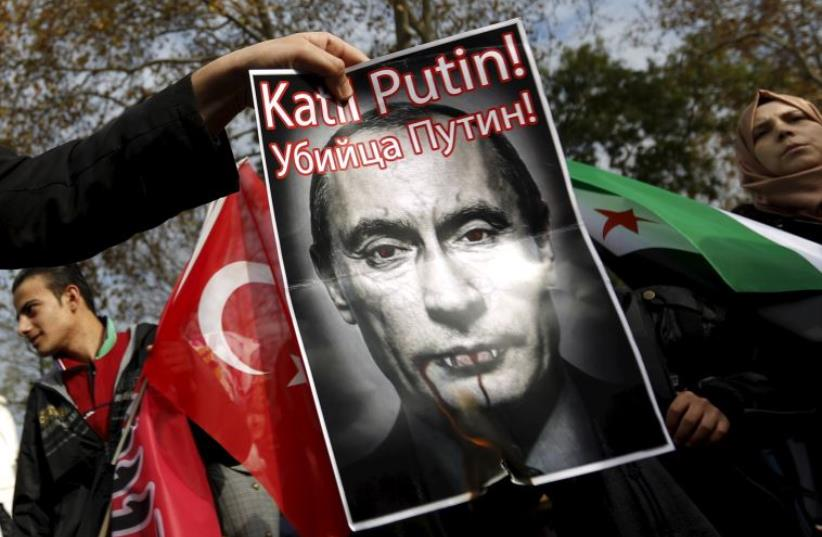 Pro-Islamist demonstrators set fire to a defaced poster of Russia's President Vladimir Putin during an anti-Russian protest in Istanbul (photo credit: REUTERS)