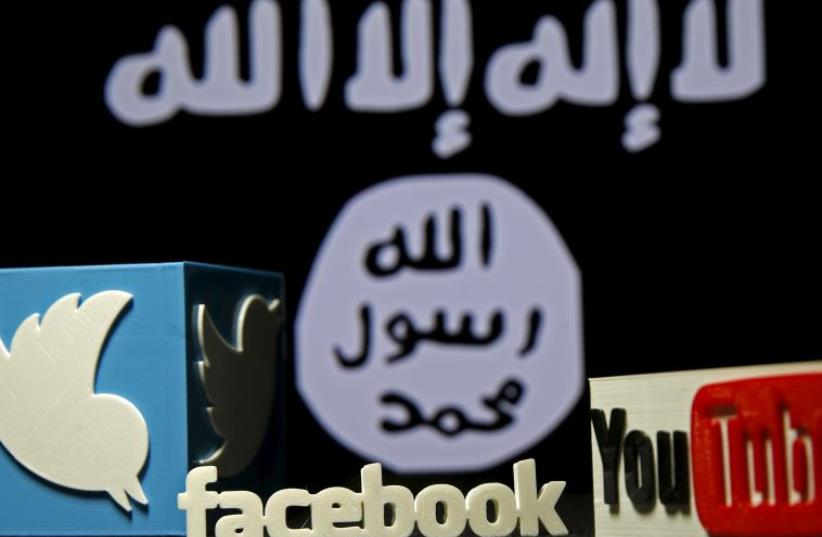 A 3D plastic representation of the Twitter and Youtube logo is seen in front of a displayed ISIS flag  (photo credit: REUTERS)