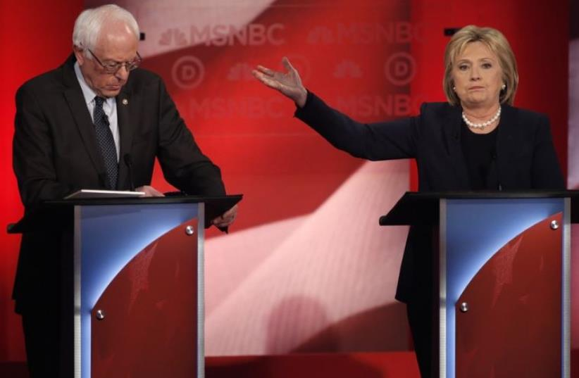 Democratic US presidential candidate and former Secretary of State Hillary Clinton (R) talks about Senator Bernie Sanders (L) during the Democratic presidential candidates debate (photo credit: REUTERS)