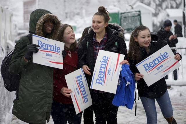 Girls supporting US Democratic presidential candidate Bernie Sanders cheer for Bernie during snowfall outside a campaign event in Exeter, New Hampshire (photo credit: REUTERS)