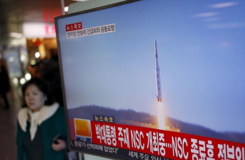 A passenger walks past a TV screen broadcasting a news report on North Korea's long range rocket launch (photo credit: REUTERS/KIM HONG-JI)