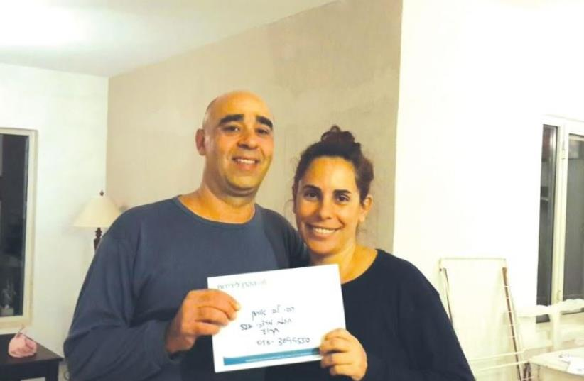 Rivi Lev-Ohayon and her husband with The Fellowship's grant for victims of terrorism. (photo credit: COURTESY IFCJ)