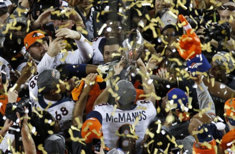 Denver Broncos' Brandon McManus (8) holds the Vince Lombardi Trophy after the Broncos defeated the Carolina Pathers in the NFL's Super Bowl 50 football game in Santa Clara, California February 7, 2016 (photo credit: REUTERS)