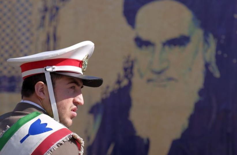 An Iranian soldier stands guard in front of a picture of Iran's late leader Ayatollah Ruhollah Khomeini during the anniversary ceremony of Iran's Islamic Revolution in Tehran, February 1, 2016 (photo credit: REUTERS/RAHEB HOMAVANDI)