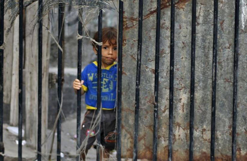 A Palestinian boy looks through the gate of his family's house at Shatti (beach) refugee camp in Gaza City  (photo credit: REUTERS)