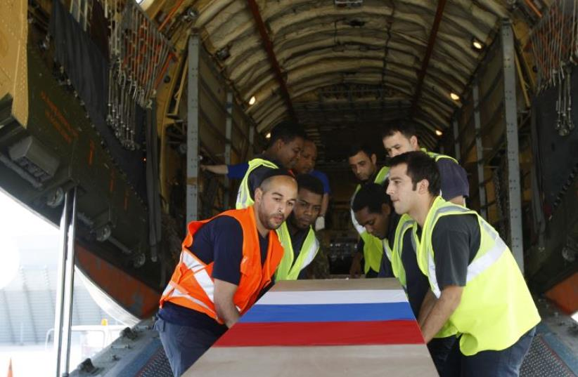 Airport workers carry one of 24 coffins of Russian tour operators, killed in a bus crash north of the Red Sea resort of Eilat, into a Russian airplane at the Ben Gurion International airport near Tel Aviv December 18, 2008. (photo credit: REUTERS)