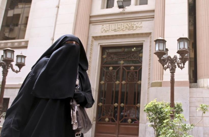 A woman walks past the Egyptian Exchange in Cairo  (photo credit: REUTERS)