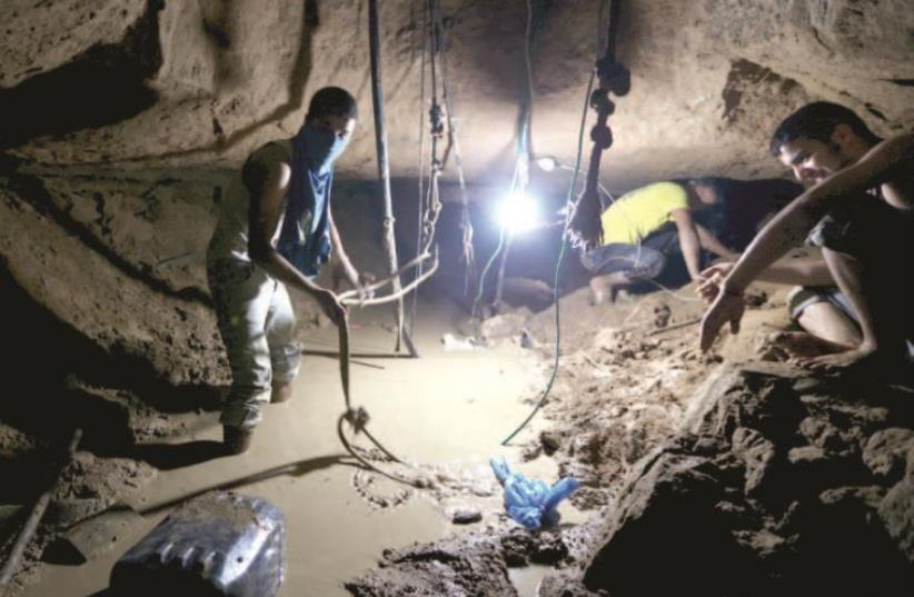 Gazans repair a smuggling tunnel, flooded by the Egyptians, beneath the border between Egypt and Gaza, November 26. (photo credit: REUTERS)