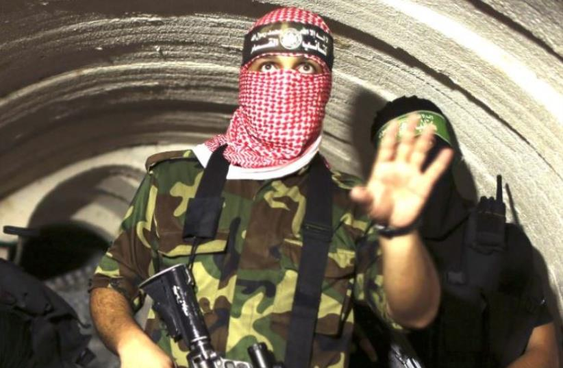 A gunman from the Izz ad-Din al- Qassam Brigades, the armed wing of Hamas, photographed inside an underground tunnel in Gaza, in 2014. (photo credit: REUTERS)