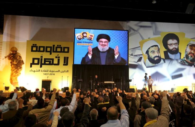Lebanon's Hezbollah leader Sayyed Hassan Nasrallah addresses his supporters through a giant screen during a rally commemorating the annual Hezbollah Martyrs' Leader Day in Beirut's southern suburbs, Lebanon February 16, 2016 (photo credit: REUTERS)
