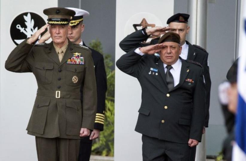 IDF chief of staff Gadi Eizenkot (R) and US Chairman of the Joint Chiefs of Staff, General Joseph F. Dunford (L), salute their national anthems during an official ceremony in Tel Aviv (photo credit: AFP PHOTO)