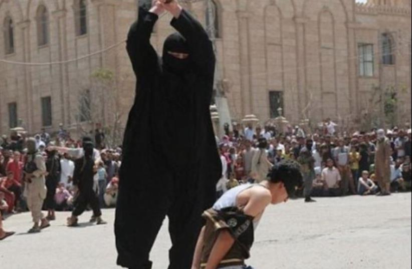 ISIS operative decapitates a young boy (photo credit: ARAB MEDIA)