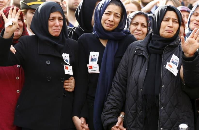 Family members of Army officer Seckin Cil, his mother Aysel (R), wife Beyza (L) and sister Busra (C), mourn during his funeral ceremony in Ankara (photo credit: REUTERS)