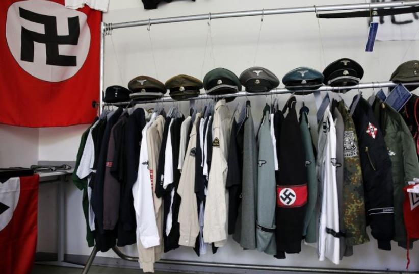 Nazi uniforms and a Swastika flag that were confiscated by the Berlin police during raids against German neo-Nazis (photo credit: REUTERS)