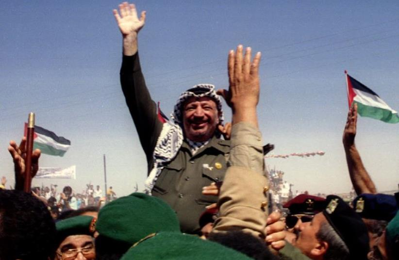 Palestine Liberation Organization chairman Yasser Arafat waves as he is briefly lifted on the shoulders of Palestinian police moments after entering the Gaza Strip in 1994 (photo credit: REUTERS)