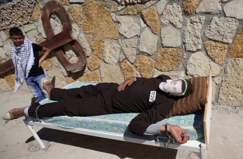 A Palestinian lies on a bed as he covers his face with a picture of Palestinian journalist Mohammad al-Qiq, who was detained by Israeli forces in November and is on an almost-three-month hunger strike (photo credit: REUTERS)