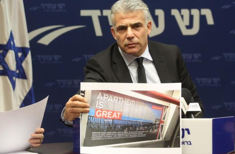 Lapid displays a picture of BDS poster  (photo credit: MARC ISRAEL SELLEM/THE JERUSALEM POST)