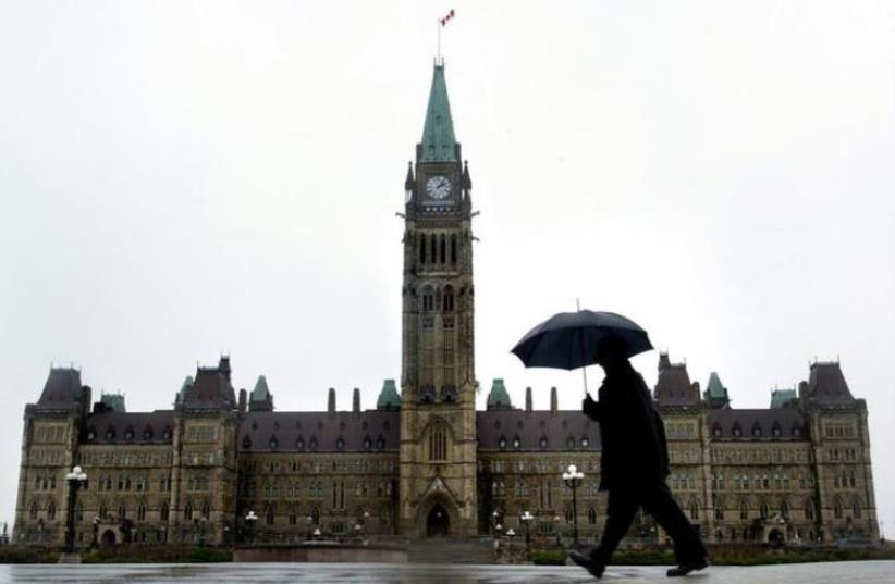 A pedestrian walks in the rain on Parliament Hill in Ottawa, Canada. (photo credit: REUTERS)