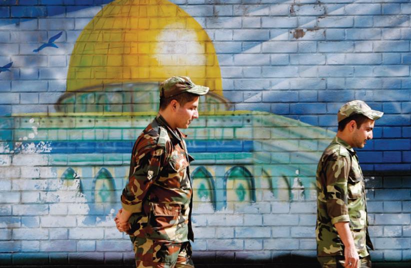 MEMBERS OF Iran's Revolutionary Guards walk past a mural of the Al-Aqsa mosque in Jerusalem in Tehran. (photo credit: REUTERS)