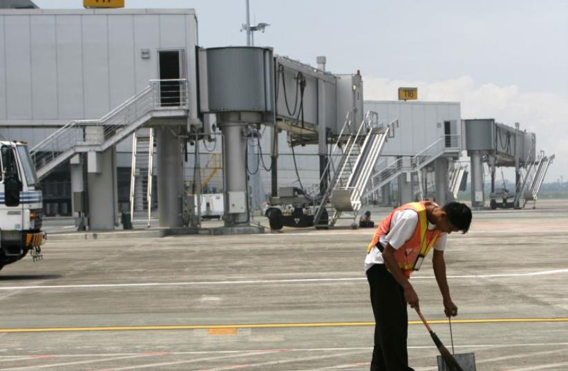 A maintenance worker sweeps the tarmac of Terminal 3 of Ninoy Aquino International Airport (photo credit: REUTERS)