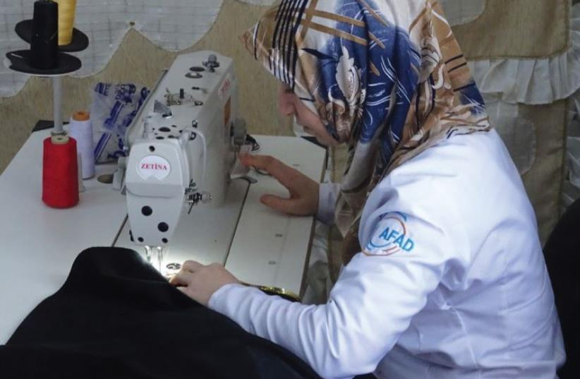 A WOMAN works at a sewing station in the Oncupinar refugee camp near Kilis at the Turkish-Syrian border.  (photo credit: SETH J. FRANTZMAN)