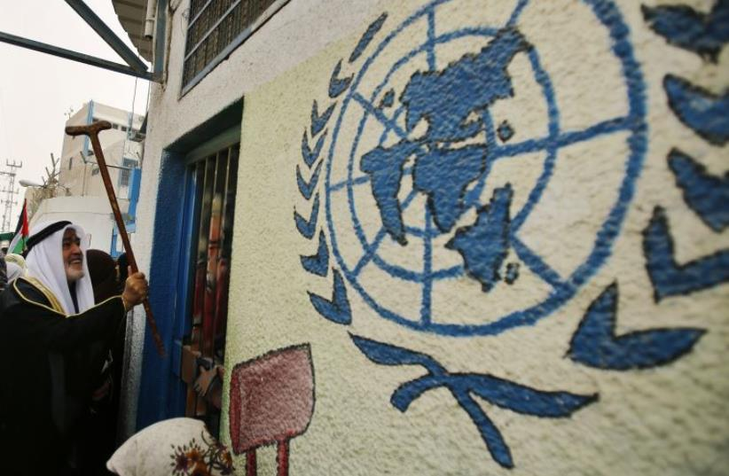 A Palestinian refugee knocks on the closed gate of the United Nations Relief and Works Agency (UNRWA) headquarters with his walking stick (photo credit: REUTERS)