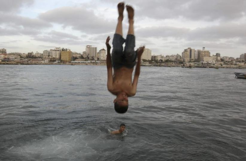 A Palestinian boy jumps into the sea at Gaza Seaport in Gaza City (photo credit: REUTERS)