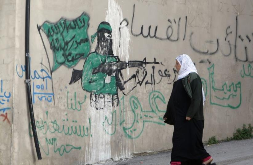 """A Palestinian woman walks past a wall with graffiti depicting a gunman from the Al-Qassam brigades, the armed wing of the Hamas movement, in the West Bank village of Awarta.  The graffiti reads """"All of us are martyrs."""" (photo credit: ABED OMAR QUSINI/REUTERS)"""