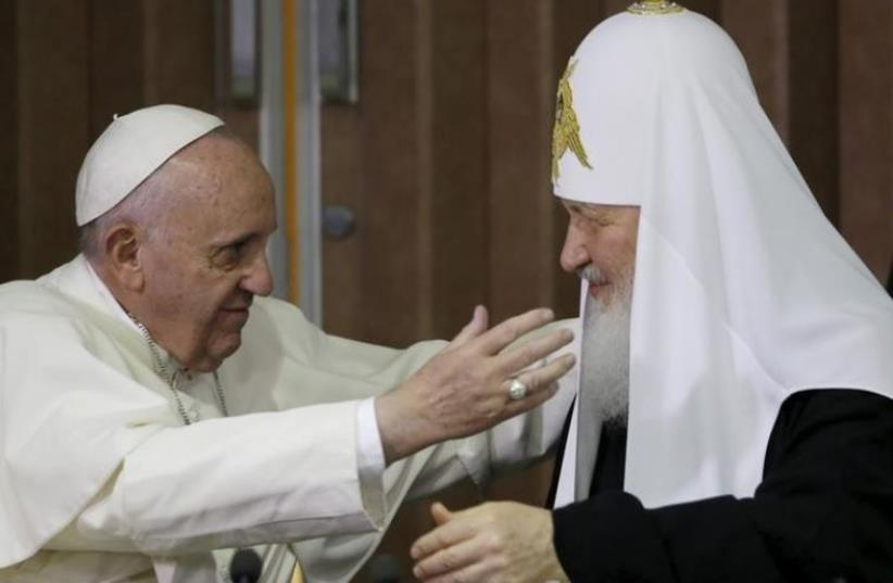 Pope Francis, left, reaches to embrace Russian Orthodox Patriarch Kirill after signing a joint declaration at the Jose Marti International airport in Havana, Cuba, Friday, February 12, 2016.  (photo credit: GREGORIO BORGIA/POOL/REUTERS)