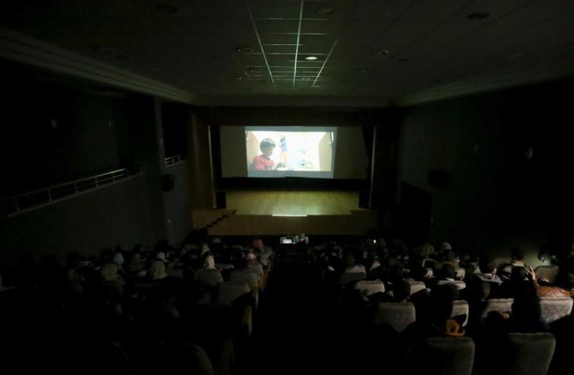 Palestinian spectators watch a movie at Red Crescent Society hall in Gaza City February 25, 2016.  (photo credit: REUTERS)