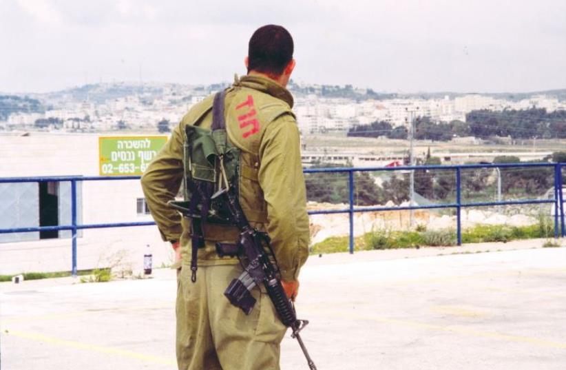 A soldier on patrol looks toward Ramallah in 2001 (photo credit: BRIAN HENDLER)