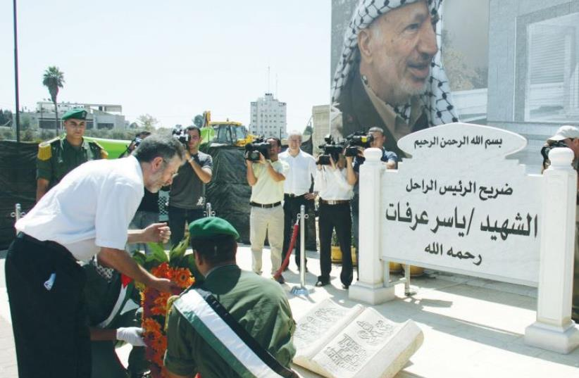 SINN FEIN LEADER Gerry Adams lays a wreath at the grave of Yasser Arafat in Ramallah in 2006 (photo credit: REUTERS)