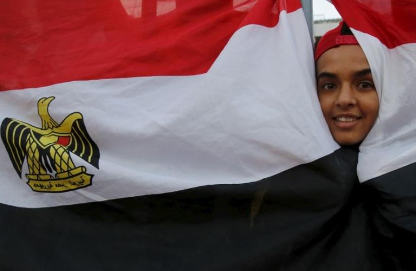 An Egyptian fan cheers behind the national flag before 2018 World Cup qualifying soccer match against Chad (photo credit: REUTERS)
