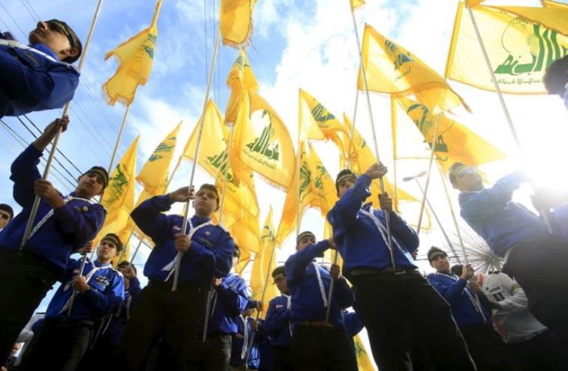 Lebanon's Hezbollah scouts carry their parties flag while marching at the funeral of three Hezbollah fighters who were killed in Syria (photo credit: REUTERS)