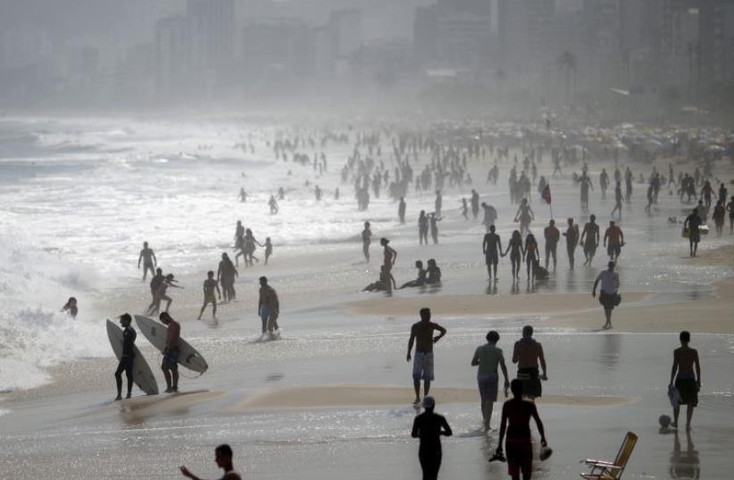 People gather in Ipanema beach in Rio De Janeiro, Brazil (photo credit: REUTERS/RICARDO MORAES)