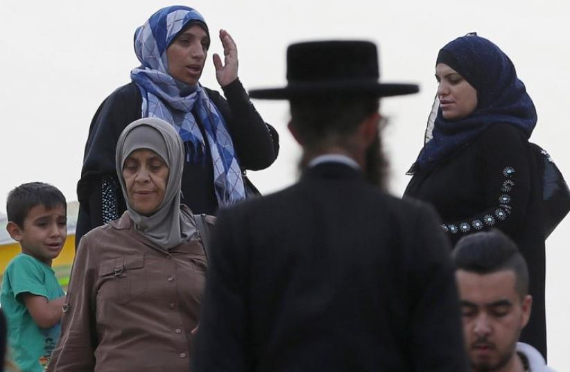 An ultra-Orthodox Jewish man walks next to Palestinian women in Jerusalem's Old City (photo credit: REUTERS)