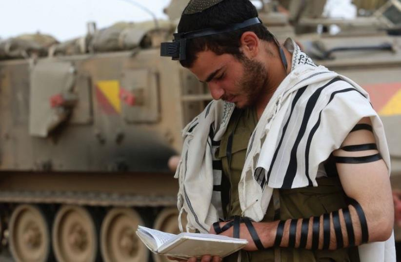 An IDF soldier prays near the Gaza border (photo credit: MARC ISRAEL SELLEM & FACEBOOK)