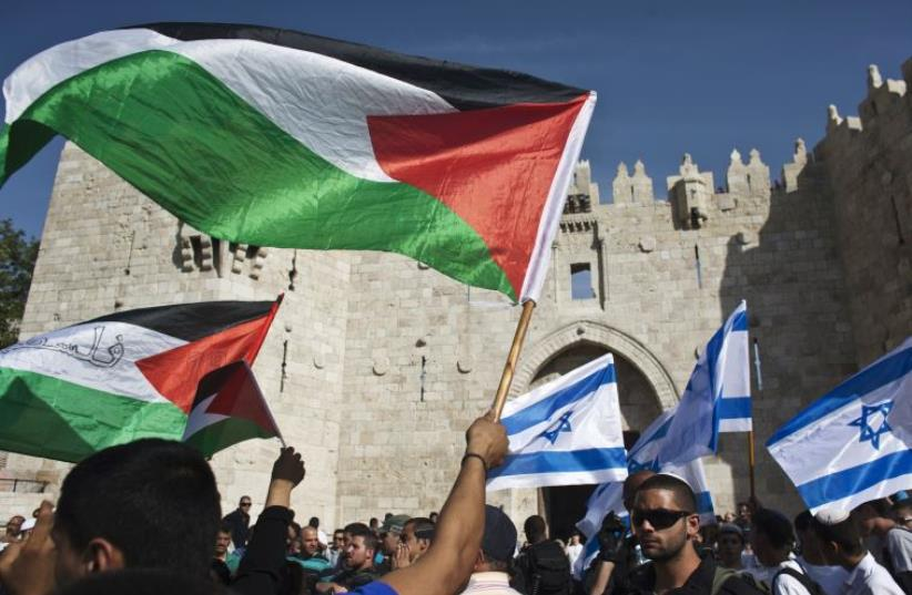Palestinian protesters wave Palestinian flags as Israelis carrying Israeli flags walk past in front of the Damascus Gate outside Jerusalem's Old City (photo credit: REUTERS)