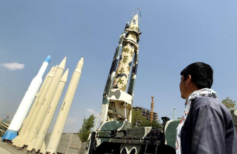 A man looks at Iranian-made missiles at Holy Defence Museum in Tehran (photo credit: REUTERS)