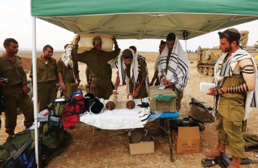IDF soldiers pray near the Gaza border. (photo credit: MARC ISRAEL SELLEM)