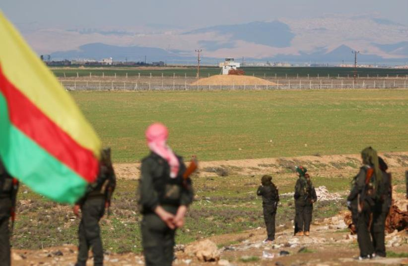 Kurdish members of the Self-Defense Forces stand near the Syrian-Turkish border in the Syrian city of al-Derbasiyah, February 9, 2016. (photo credit: RODI SAID / REUTERS)