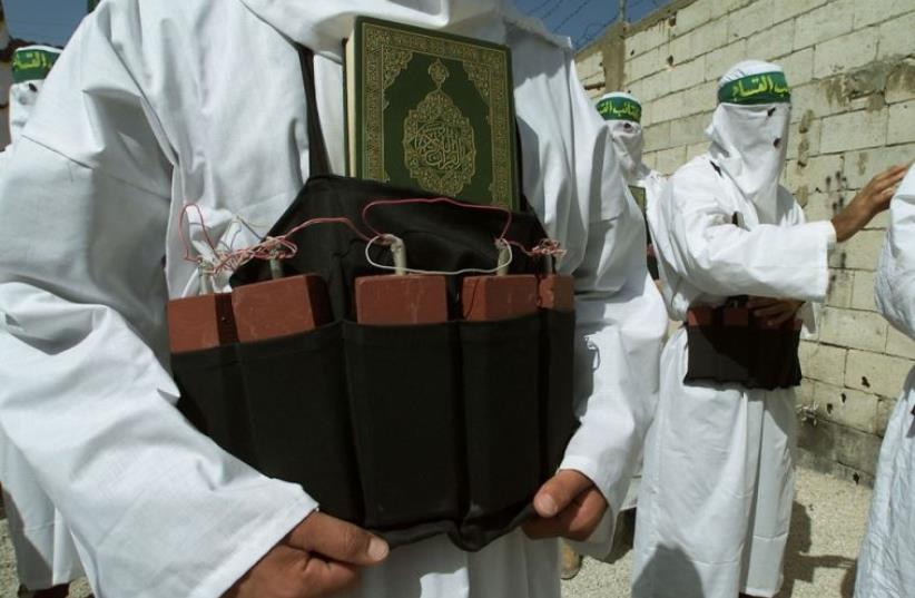 A Palestinian from the Islamic group Hamas carries the holy book the Koran tucked into a belt of simulated explosives (photo credit: REUTERS)