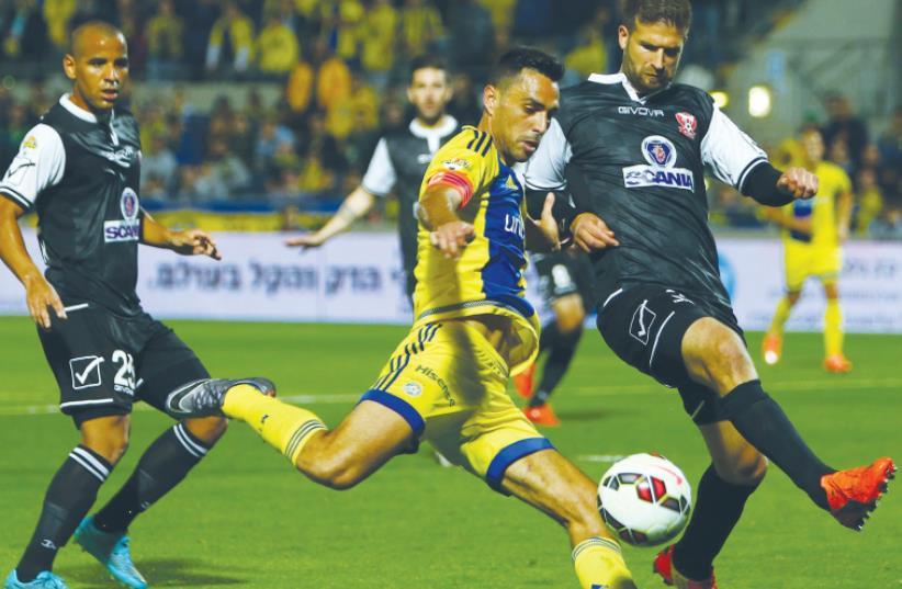 Maccabi Tel Aviv captain Eran Zahavi (center) scored the only goal in last night's 1-0 win over Bnei Sakhnin at Bloomfield Stadium, bringing the yellow-and-blue within a single point of leader Hapoel Beersheba. (photo credit: UDI ZITIAT)