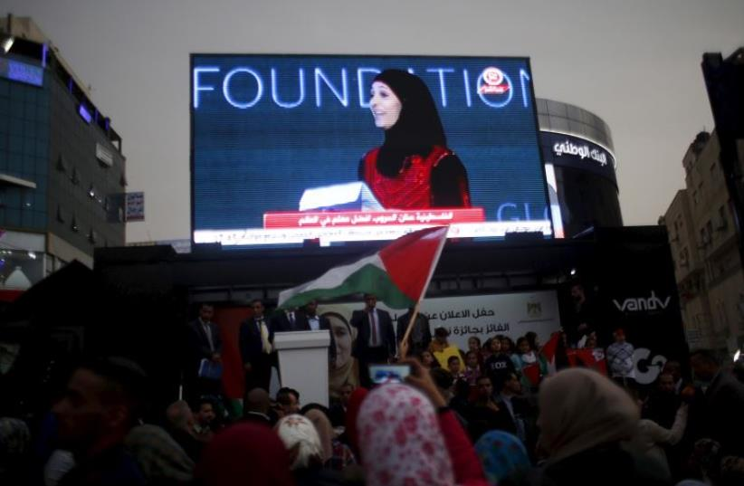 Palestinians watch on a screen in the West Bank city of Ramallah March 13, 2016 as primary school teacher Hanan al-Hroub receives the Million Dollar Teacher award.  (photo credit: REUTERS)