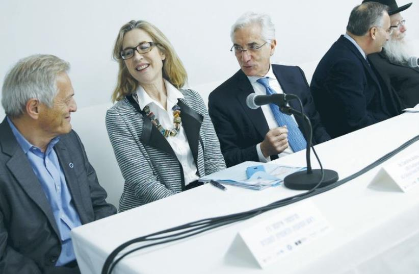 RONALD COHEN (center), the chairman of a global steering group on social-impact investing, sits next to Caroline Anstey, the head of UBS and Society, a global initiative launched by the Swiss investment bank in 2014 that covers activities in sustainable investing and philanthropy, during a news conf (photo credit: REUTERS/BAZ RATNER)